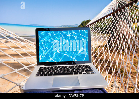 laptop in hammock on the beach - Stock Photo