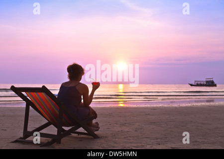 middle age woman with cocktail enjoy sunset on the beach - Stock Photo