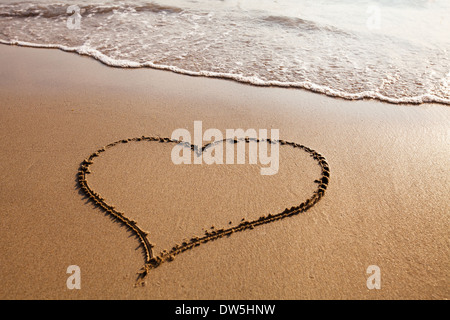 Heart drawn on the sandy beach, valentines day background - Stock Photo