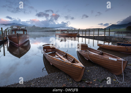 Boats moored on Derwent Water at dawn, Keswick, Lake District, Cumbria, England. Autumn (October) 2012. - Stock Photo