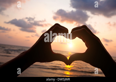 heart from hands of couple on the beach - Stock Photo