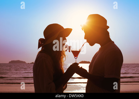 share the pleasure, couple drinking cocktail on the beach - Stock Photo