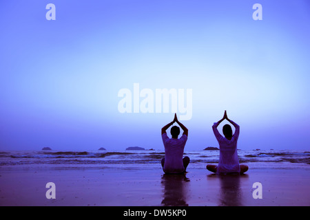 family yoga on the beach at sunset - Stock Photo