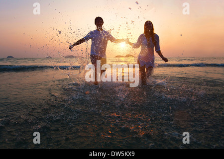 happy couple enjoy sunset on the beach - Stock Photo