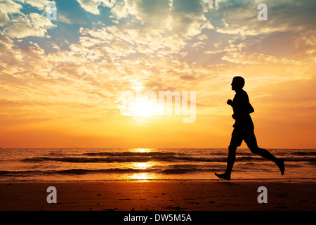silhouette of man running on the beach at sunset - Stock Photo