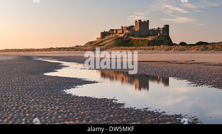 Bamburgh Castle and reflection in Bamburgh Beach tidal pools, Northumberland, England. Spring (April) 2013. - Stock Photo