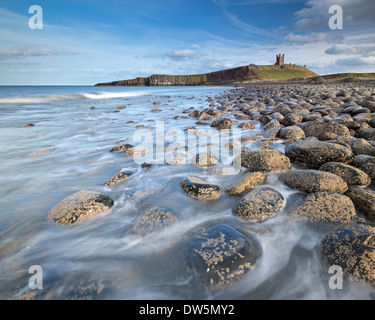 The ruins of Dunstanburgh Castle overlooking the boulder strewn shores of Embleton Bay, Northumberland, England. - Stock Photo