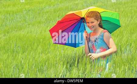 girl with umbrella on field in summer time - Stock Photo