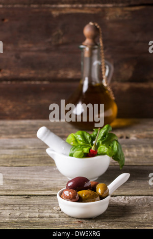 Mix of olives with fresh basil in white mortar and vintage bottle of olive oil on old wooden table - Stock Photo