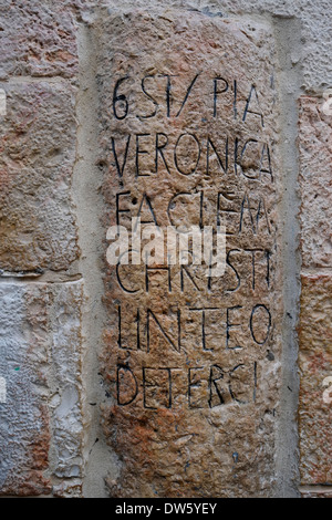 An old stone indicating the 6th station of the cross with an inscription in Latin which reads Veronica wipes the - Stock Photo