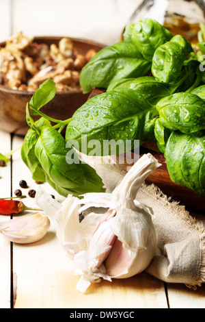 Bunch of fresh basil, bowl of walnuts, pepper and garlic served on white wooden table. See series - Stock Photo