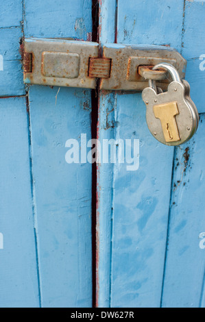 Close up of a padlocked door, not very secure. A thief could probably jemmy it open in no time - Stock Photo