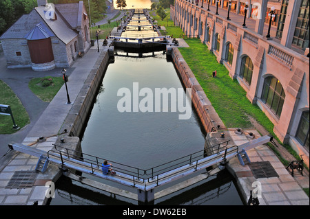 A solitary figure sitting on one of the lock gates at the start of the Rideau Canal in Ottawa, Canada. - Stock Photo