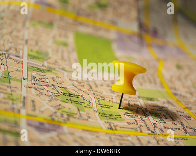 Yellow pushpin on a map - Stock Photo