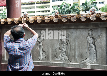 Buddhists pray and burn incense at Kwan Im Thong Hood Cho Temple in Singapore. - Stock Photo