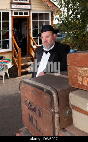 A man in 1940's costume leaning on some luggage at Weybourne Railway Station - Stock Photo