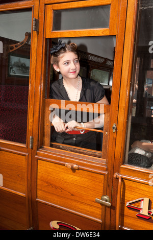 A young woman in 1940's costume looks out of a railway carriage's open window - Stock Photo