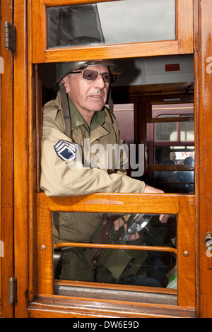 A man in 1940's solider costume looking out of a railway carriage window holding a camera - Stock Photo