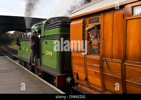 A Soldier  wearing a  1940's Captain's uniform looks out from a railway carriage of a steam train - Stock Photo