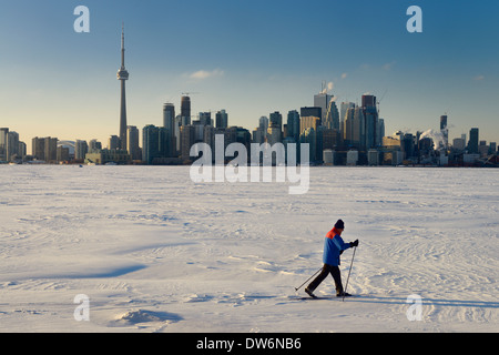 Man cross country skiing on frozen Lake Ontario with Toronto city skyline in winter from Toronto Islands Canada - Stock Photo