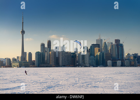 Young man snowkiting with snowboard on frozen Lake Ontario with Toronto city skyline in winter - Stock Photo