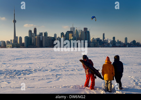 Young friends watching snowkiter with board on frozen Lake Ontario with Toronto city skyline at Toronto Islands - Stock Photo