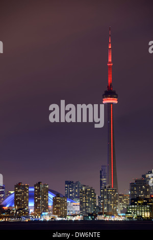 Toronto CN tower with red lights and Rogers Centre Skydome at night in winter - Stock Photo