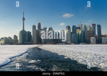 Toronto city skyline with ice breaking path of Wards Island Ferry on frozen Lake Ontario - Stock Photo
