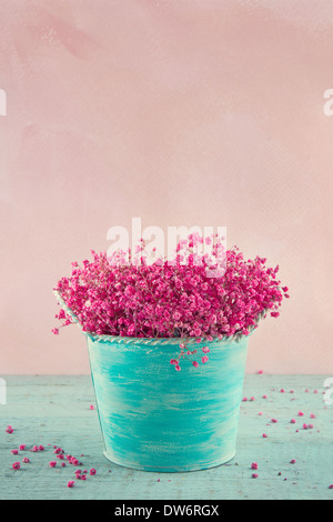 Pink dried baby's breath flowers in a blue vase on wooden vintage background - Stock Photo