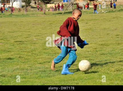 Boys wearing traditional clothes play football in school playground, village of Sakteng on Merak Sakteng trek, Eastern - Stock Photo