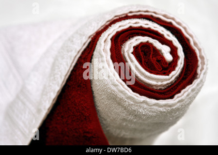 warm, dry, rolled up red and white towels in a spa - Stock Photo