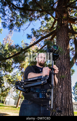 A young man with a DSLR steadycam rig - Stock Photo