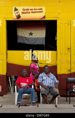 Friends sitting outside a bar in Cape Coast, Ghana - Stock Photo