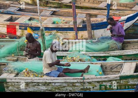 Fishermen mending fishing nets in Elmina Harbour, Elmina, Cape Cost, Ghana - Stock Photo