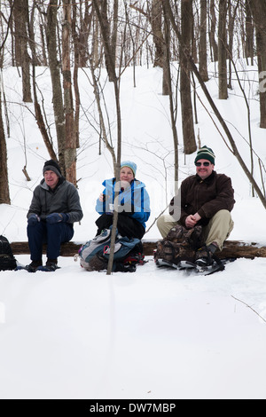 Winter hikers relax and rest along a snow-covered trail on Mount Greylock, Adams, MA. - Stock Photo