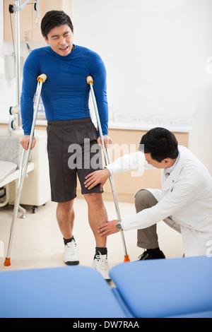 Doctor examining patient's leg - Stock Photo