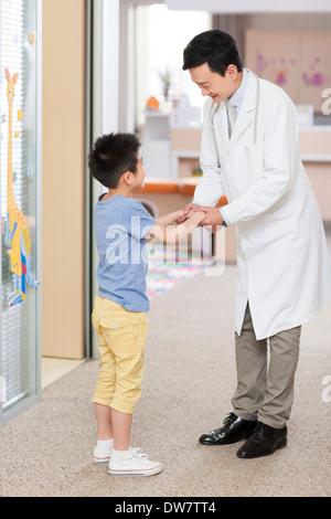 Doctor talking to little boy in hospital - Stock Photo