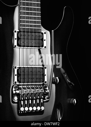 Artistic closeup of an electric guitar Ibanez with chrome parts on black background black and white photo - Stock Photo