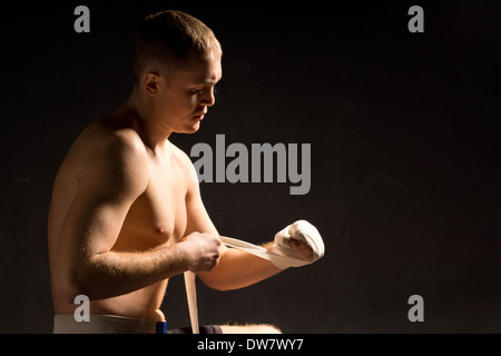 Muscular young boxer preparing for a fight putting on the bandages on his knuckles as he sits in the shadows - Stock Photo