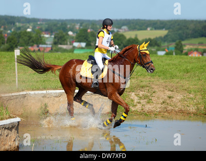 Three-day-event: horse and rider race through the water to the next jump - Stock Photo