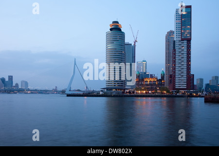 City of Rotterdam downtown skyline in the evening and Erasmus Bridge on Nieuwe Maas (New Meuse) river in Netherlands.