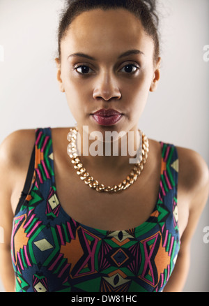 Close up image of smart young lady looking at camera. Hispanic female model starting at you on grey background - Stock Photo