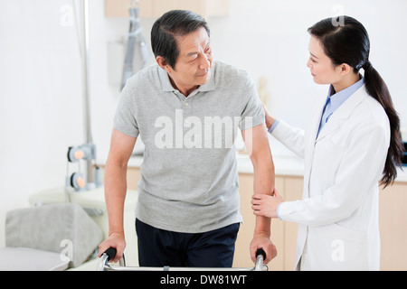 Doctor helping patient with walker - Stock Photo