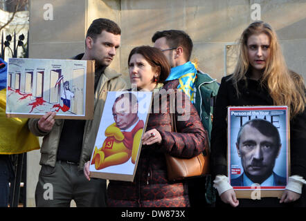 Prague, Czech Republic. 2nd March, 2014. Protesters hold placards with cartoons of Russian President Vladimir Putin - Stock Photo