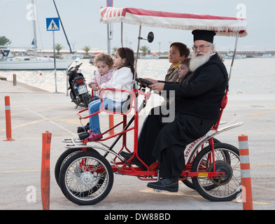 A priest and children on a tourist quadricycle in Nafplio harbour, Argolid, Peloponnese, Greece - Stock Photo