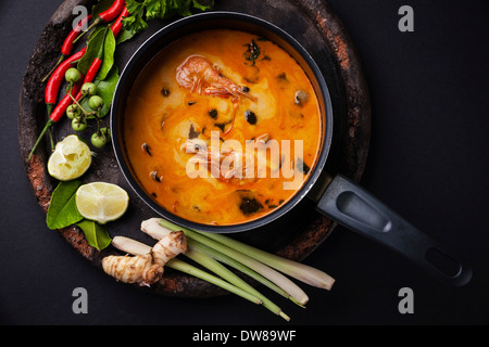 Spicy Thai soup Tom Yam with Ingredients on dark background - Stock Photo