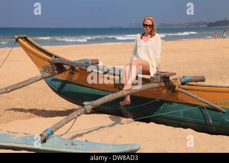 Sri Lanka, Bentota, beach, outrigger canoe, western tourist, - Stock Photo