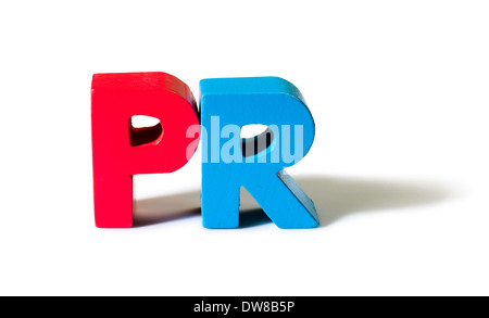 Multicolored text PR made of wood. White background - Stock Photo