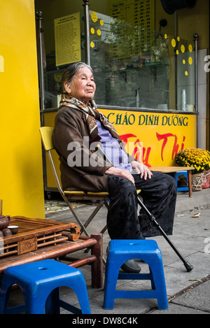 HANOI, VIETNAM- JANUARY 27: An elderly Vietnamese woman sitting on the street in the countries capital city Hanoi - Stock Photo