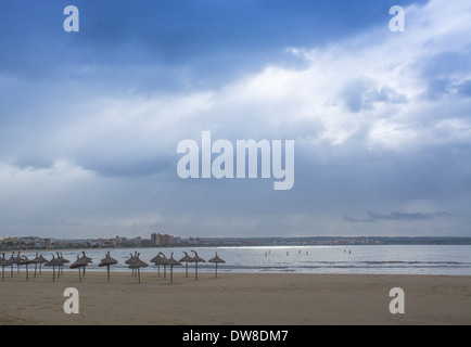 November scene in Playa de Palma with parasols, paddle surfers and hotels around the bay in late afternoon beautiful - Stock Photo